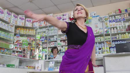 gyógyszerész : SIMFEROPOL, CRIMEA - CIRCA OCTOBER 2015: Pharmacy store interior. Pharmacist and happy customer. Woman performing traditional indian dance at the drugstore.