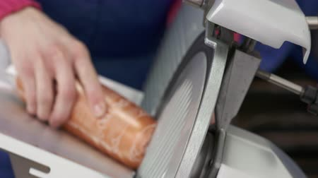 slicer : YEVPATORIA, CRIMEA - CIRCA DECEMBER 2017: Professional electric food slicer. Closeup of meat slicing machine. Processed meat products of the plant Eupatoria Sausages. Female chef slices boiled sausage Stock Footage