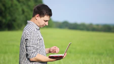 trigo sarraceno : The caucasian male brunette farmer on the field works with a laptop. Scientist working in the field with agricultural technology.