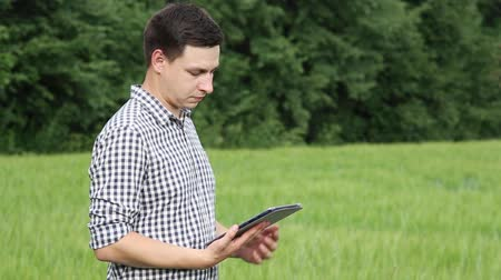 trigo sarraceno : The caucasian male brunette farmer on the field works with a tablet. Scientist working in the field with agricultural technology. Vídeos