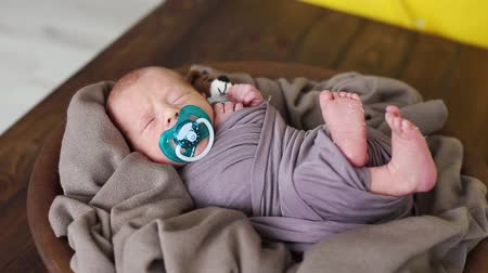 first born : The newborn boy sleeps in a plate with a brown cloth and moves his foot Stock Footage