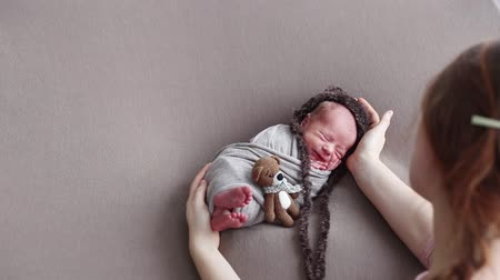 first born : The Caucasian woman photographer lulls the newborn, wrapped in a cocoon and dressed in a teddy bear hat