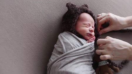 first born : The woman photographer tied the strings on a hat of newborn boy wrapped in a cocoon Stock Footage