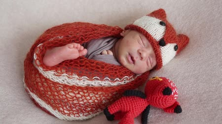 first born : A newborn boy wearing a fox dress is sleeping on a background of a stretched canvas Stock Footage