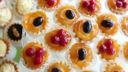 tort weselny : Cakes with fruit and berries are laid out in a showcase Wideo