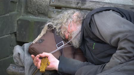 pastor : Paris, France June 25, 2019: Drunk priest with a cross in his hand sleeping on the street