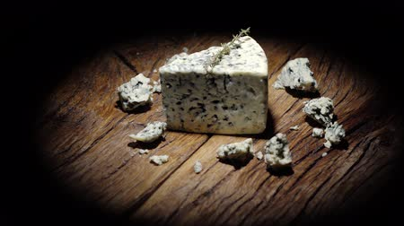 grissini : Danish Blue Cheese with pieces rotating around its own axis. On a old wooden table and black background. 4K video.