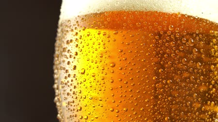 frescura : Glass of beer. Close up 4K video. Black background.