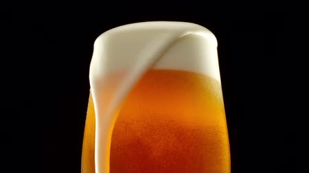 Stream of beer pours into a rolling beer glass. Close up 4K video. Macro shooting.