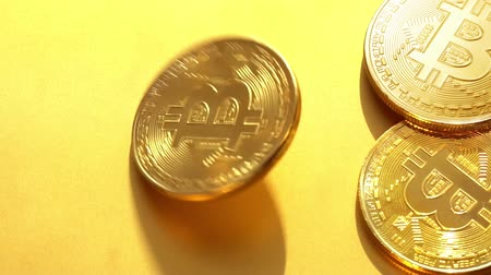 Coin golden bitcoin rotation, twist and falls on a golden background. Slow motion video 120 fps. Wideo