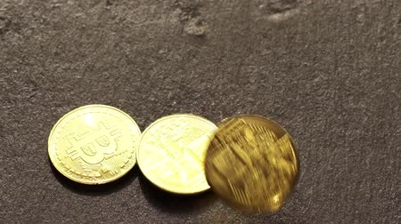 Coins golden bitcoin fall and twist on the graphite surface. Slow motion video. 120 fps.