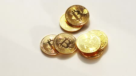 Coins golden bitcoin fall and twist on the white surface. Slow motion video. 120 fps. Wideo