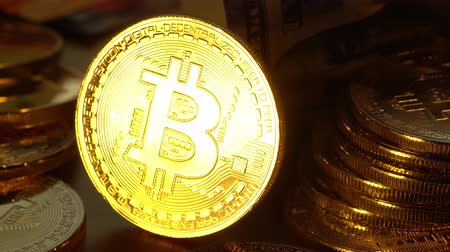Bitcoin coin is glowed with golden light and gradually fades. Macro shot. 4K looped video.