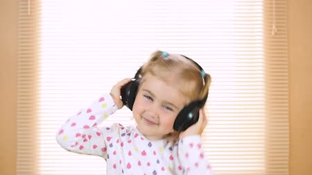 fejhallgató : little girl listening to music on headphones. home, technology and music