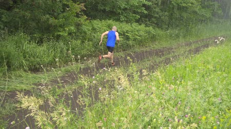aventura : Slow motion. Male runner exercising and training outdoors in nature. traill-running.Rainy day