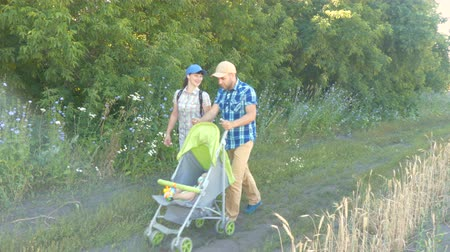 sáně : Happy family couple push green baby stroller on rural road in sunny summer day. Healthy leisure in fresh air. Dostupné videozáznamy