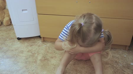 len : Baby little girl crying sits on the floor in room. Dostupné videozáznamy