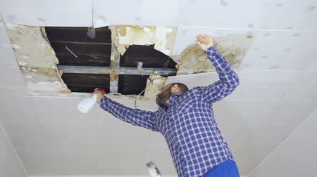 bakım : man cleaning mold on ceiling.Ceiling panels damaged huge hole in roof from rainwater leakage.Water damaged ceiling. Stok Video