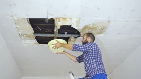 повреждение : Man Collecting Water In basin From Ceiling. Ceiling panels damaged huge hole in roof from rainwater leakage.Water damaged ceiling.