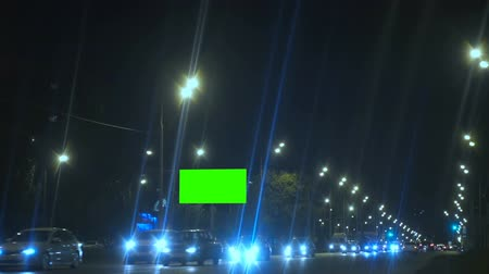 billboards : Billboard with a Green Screen on Night Street. Night city street with cars. Light car headlight lamp on the roadside in the city.