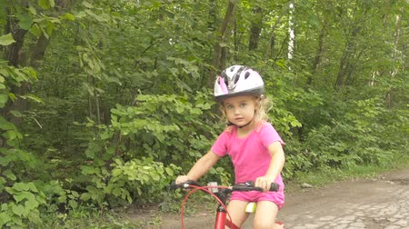 kolo : Happy child riding a bike in outdoor. Cute kid in safety helmet biking outdoors. Little girl on a red bicycle Healthy preschool children summer activity.