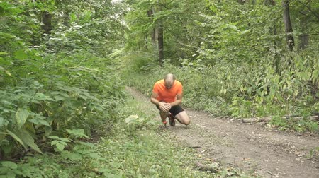 diz : Young Man Having a Cramp While Jogging. Stop And To Massage the Knee. Man Running Cross Country In Summer Forest.
