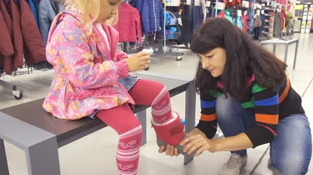 booties : A little baby girl and his mother are choosing warm winter rubber boots in the store.