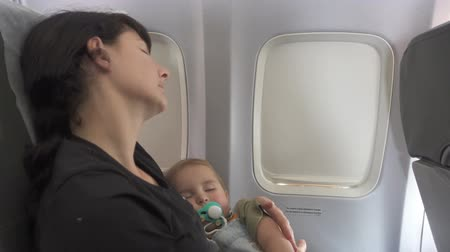 emzik : Mother with a baby sleeping in the aircraft cabin, sitting around illuminator. A child with a pacifier.