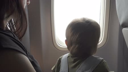 points of interest : Son baby sitting on mothers lap in plane and looking in view from illuminator. Stock Footage