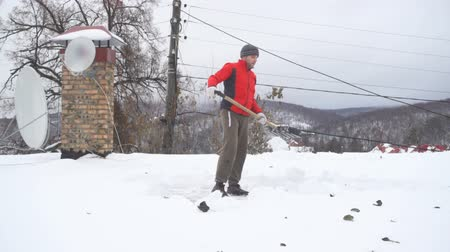 deep snow : Slow Motion Man with a shovel removing snow from a roof. Caucasian men using to shovel heavy snow off roof. People with plastic shovel tool push clean snow from roof.