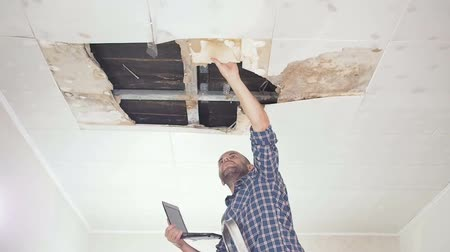 opravář : young man makes an emergency inspection of ceiling and use laptop PC. public utilities. Ceiling panels damaged huge hole in roof from rainwater leakage.Water damaged ceiling, Insurance agent.