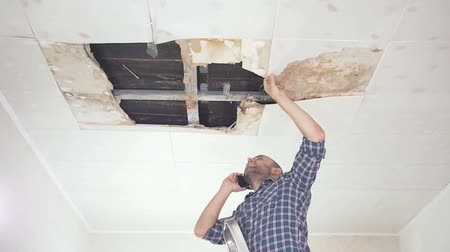 opravář : Young man call on the phone in the Service, and public utilities. Ceiling panels damaged huge hole in roof from rainwater leakage.Water damaged ceiling, Insurance case.