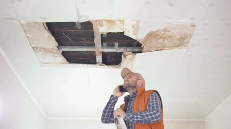 zastřešení : Young man call on the phone in the Service, and public utilities. Ceiling panels damaged huge hole in roof from rainwater leakage.Water damaged ceiling, Insurance case.