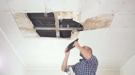 повреждение : young man makes an emergency inspection of ceiling and use Tablet PC. public utilities. Ceiling panels damaged huge hole in roof from rainwater leakage.Water damaged ceiling, Insurance agent.
