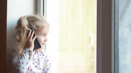 telefon : Blonde little girl talking on the phone. Sitting on the window sill. The child looks out of the window. Stock mozgókép