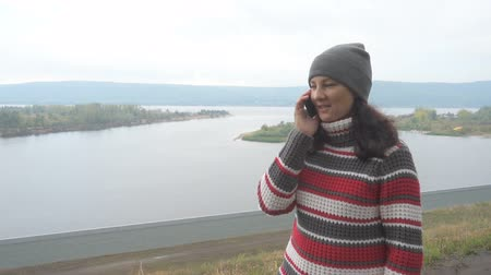 поход : Young woman talking on the phone outdoors on background of the river and mountains. Autumn day.