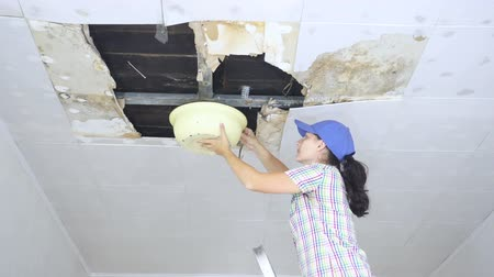 zastřešení : Young Woman Collecting Water In basin From Ceiling. Ceiling panels damaged huge hole in roof from rainwater leakage.Water damaged ceiling.