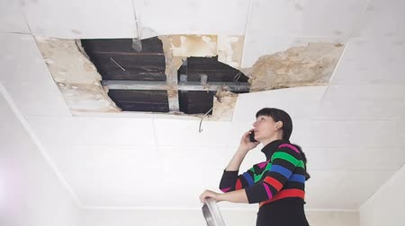 çatlaklar : Young Woman call on the phone in the Service, and public utilities. Ceiling panels damaged huge hole in roof from rainwater leakage.Water damaged ceiling, Insurance case.