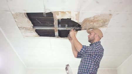 opravář : young man makes an emergency inspection of ceiling and use Tablet PC. public utilities. Ceiling panels damaged huge hole in roof from rainwater leakage.Water damaged ceiling, Insurance agent.