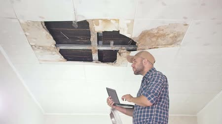 повреждение : young man makes an emergency inspection of ceiling and use laptop PC. public utilities. Ceiling panels damaged huge hole in roof from rainwater leakage.Water damaged ceiling, Insurance agent.