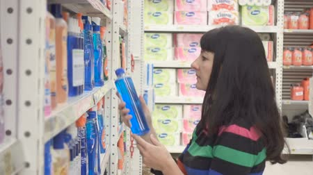 cleaning products : Young woman choosing household detergents in the section of home care in the supermarket. Great assortment on the shelves Stock Footage