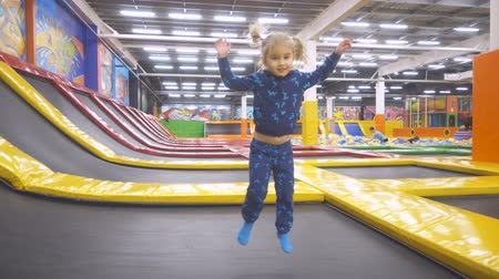 pigtailler : Little Child Jumping At Trampoline In Indoors Playground. Active Toddler Girl Having Fun At Sport Center. Slow Motion Stok Video