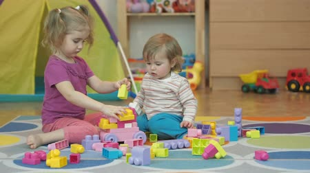 przedszkole : Boy and Girl Build Toy. Children Kid and Baby Play With Blocks. Educational Toys for preschool and kindergarten child. Brother and Sister Playing Plastic Designer Sitting On the Floor. Wideo