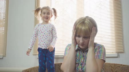 bosszús : Cute little girl jumping on the bed. Mother calms unruly child. A hyperactive kids. Preschool Education.