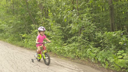 biztonság : Happy child riding a bike in outdoor. Cute kid in safety helmet biking outdoors. Little girl on a red bicycle Healthy preschool children summer activity.