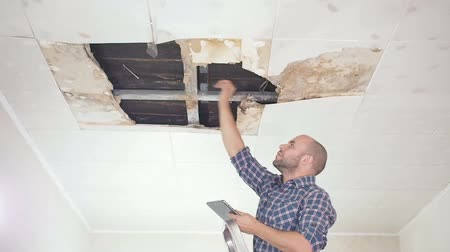 tető : young man makes an emergency inspection of ceiling and use Tablet PC. public utilities. Ceiling panels damaged huge hole in roof from rainwater leakage.Water damaged ceiling, Insurance agent.
