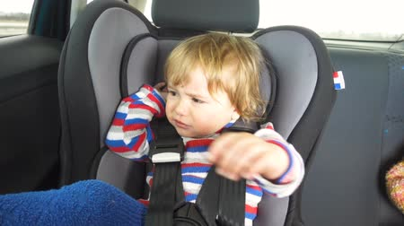 carseat : Small child cries and screams in the car. Crying baby boy in car seat. Crying child.
