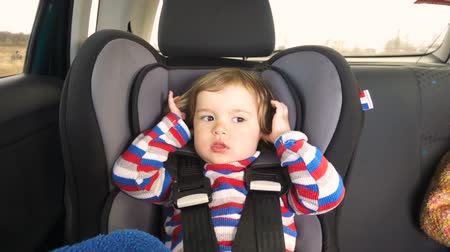 baby chubby : Boy baby kid in a striped jacket in the childrens car seat in the car rides. Little baby child infant an automobile armchair
