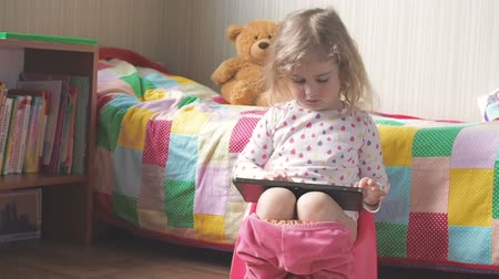 сидеть : Little girl sitting on the potty beside the bed and playing on a tablet PC.
