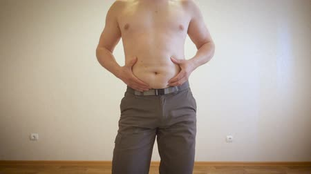 жир : A man is posing showing a fat stomach. Fat man massages his belly.